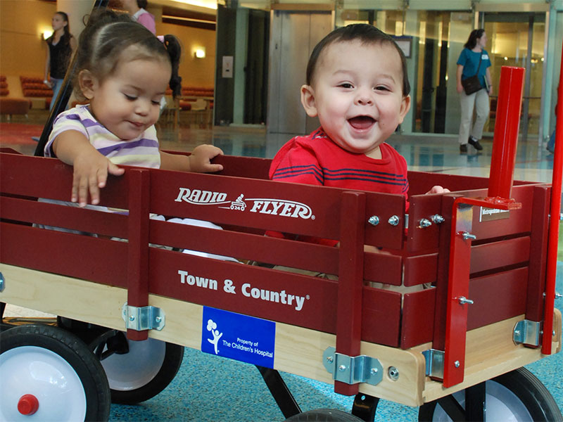 Two toddlers ride in a red wooden wagon in the Children's Hospital Colorado atrium.