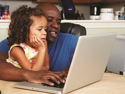 A father and daughter use a laptop together